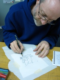 Michael is drawing an image in pencil; the waxed copper plate is underneath the paper. The pencil is making an impression through the paper into the wax, lifting the wax off the copper plate. The acid will etch into these lines; the rest of the plate is protected by the wax, which we will wipe off when we take it out of the acid bath.