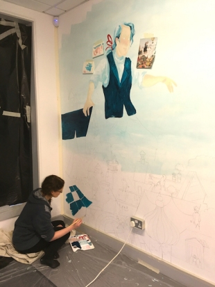 Lauren on day one, getting the basic colours in, mixing them so they mimic the watercolour original in the book. Lauren used a projector to blow up an image from her book.